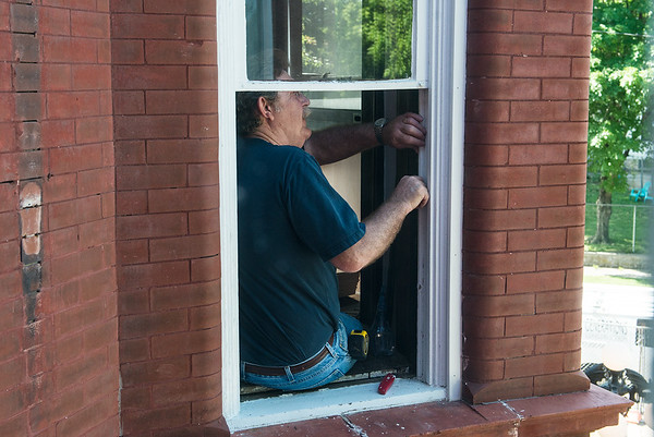 Bob Yapp gives instructions on removing a window at the Schifferdecker House on Friday.<br /> Globe | Roger Nomer