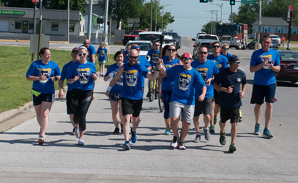 Cail Tingle, 16, and Teague Braker, Webb City Police communications supervisor and Special Olympics organizer, near the end of the Webb City leg of the 2018 Law Enforcement Torch Run in King Jack Park on Tuesday.<br /> Globe | Roger Nomer