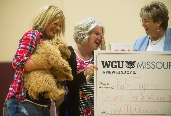 Royal Heights Elementary teacher Kate Tupper, center, wipes away a tear as WGU Chancellor Angie Besendorfer presents her with a check for training Bridget, held by school counselor Nasha Robinson, on Monday.<br /> Globe | Roger Nomer