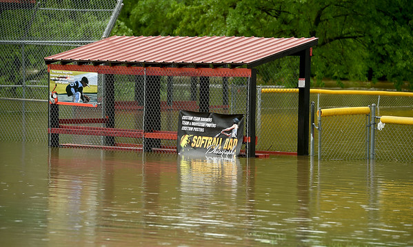 A dugout in Frank Dean Sports Complex lay submerged with near Carl Junction's Center Creek Park on Thursday morning.<br /> Globe | Laurie Sisk