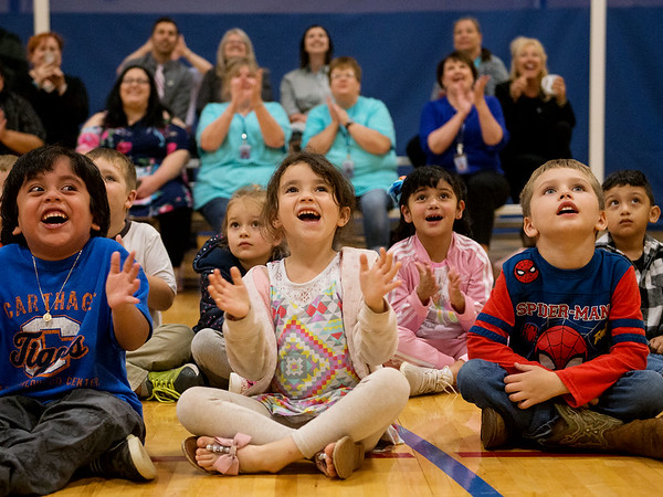 Carthage Early Childhood Center students, from left, Mathew Guillen, Nora Haines and Jonathan Boothe watch as their mural is unveiled at the Fair Acres Family YMCA at Carthage on Thursday.<br /> Globe | Roger Nomer