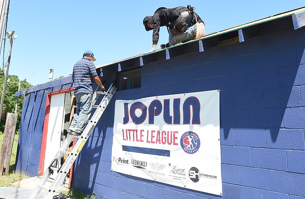 Volunteers from Torres Roofing help install a new roof on a storage building with materials donated by Tamko Roofing at the Landreth Park Little League Fields on Thursday. The fields and structures at the park suffered flood damage during heavy rains last week. From the left: Catalino Hernandez and Elmer de la Cruz.<br /> Globe | Laurie Sisk