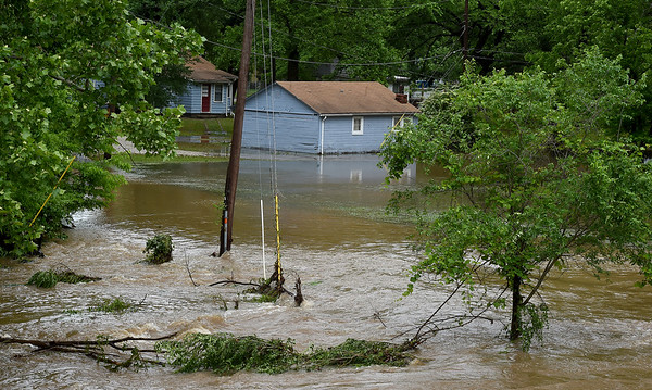 Receding waters flow by a house on Jaccard Street in the Royal Heights neighborhood after Turkey Creek flooded the neighborhood on Thursday morning. Now receded, the water was once several feet high on the pictured house.<br /> Globe | Laurie SIsk