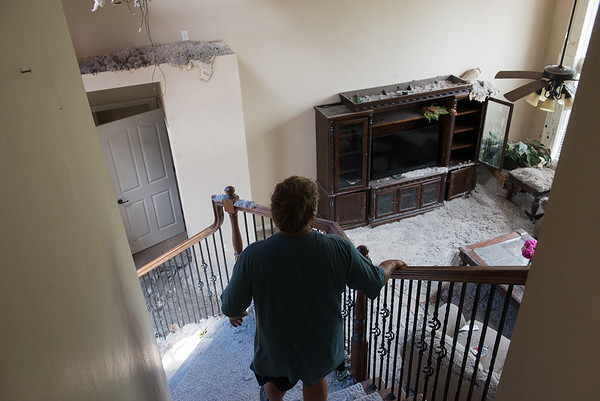 Clark Wilson walks down the stairs of his tornado-damaged house in Briarbroook on Tuesday.<br /> Globe | Roger Nomer