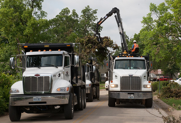 Workers with Asbell Trucking clear tree debris from Briarbrook on Tuesday.<br /> Globe   Roger Nomer