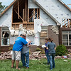 Homeowner Keith James, center, gets a hug from friend Clive Veri, left, after friends and family helped him move furniture from his tornado-damaged house in the Briarbrook neighborhood of Carl Junction on Thursday.<br /> Globe | Roger Nomer