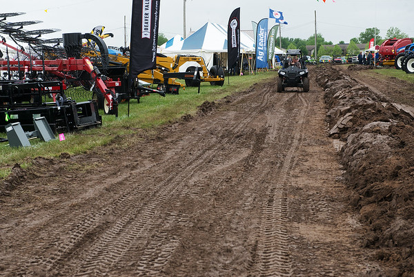 Farm equipment is displayed along a muddy road at the Four States Farm Show on Friday near Pittsburg.<br /> Globe | Roger Nomer