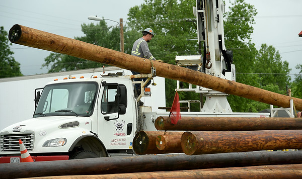Crews from Neosho's Mo Hawk Electric load new utility poles at a staging area on Pennell Street in Carl Junction on Thursday morning.<br /> Globe | Laurie Sisk
