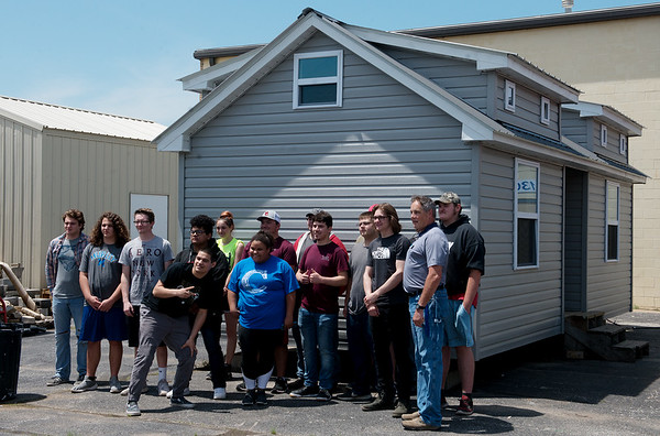 Construction students pose for a photo for Missouri State Rep. Dirk Deaton, the new owner of one of the tiny houses auctioned on Tuesday at Crowder Technical Education Center.<br /> Globe | Roger Nomer