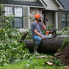Jason Waldon wipes away sweat while taking a break with his chainsaw in the Briarbrook neighborhood of Carl Junction on Thursday.<br /> Globe | Roger Nomer