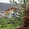 A volunteer helps clear trees from Isaiah Basye's house in the Briarbrook neighborhood of Carl Junction on Thursday.<br /> Globe | Roger Nomer