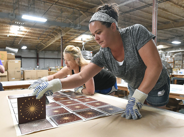 Christy Duley, left, and Melinda Burton flip hot tiles as they come off a heat press on Tuesday at Images in Tile.<br /> Globe | Laurie Sisk