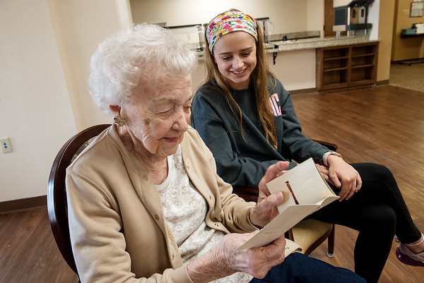 Corrinne Grosse looks over her graduation announcement from her time at Carl Junction High School with her great granddaughter Maici Craig on Friday at Spring River Christian Village.<br /> Globe | Roger Nomer