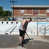 Axle Vene, pool operator, power washes the deck of the Schifferdecker Pool on Friday.<br /> Globe | Roger Nomer