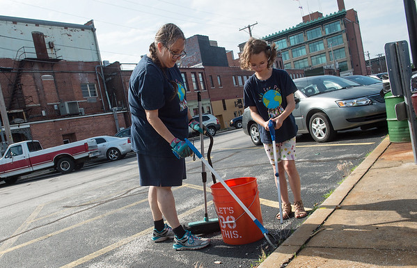 Laura Potts and her daughter Calypso Ruddick, 9, with Kids for Peace, help clean a downtown parking lot on Friday during a cleanup event held by the Downtown Joplin Alliance.<br /> Globe | Roger Nomer