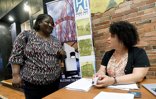 From the left: Lisa Colbert visits with Dola Flake during the Post Art Library's East Town Show and Tell project on Tuesday night at Boookhouse Cinema.<br /> Globe   Laurie SIsk