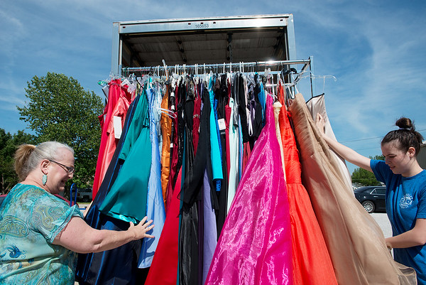 Pamela Hosp, left, and Rebecca Freitas help load a rack of dresses on Friday during moving day for Operation Fairy Godmother from the former Duenweg School.<br /> Globe | Roger Nomer