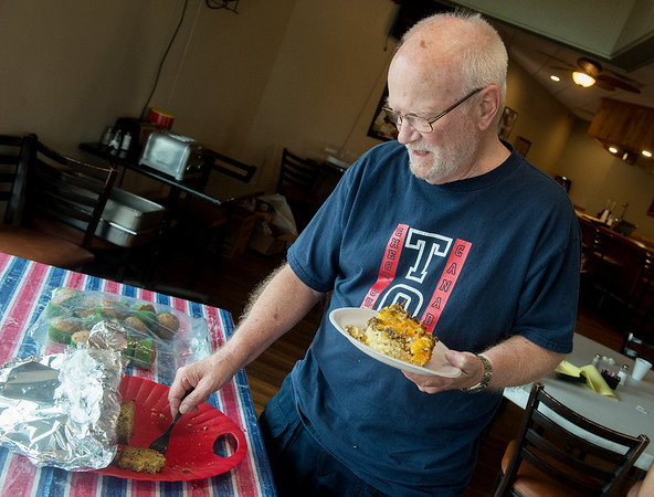 Gene Le Riche tries food brought in by community volunteers to the Briarbrook Country Club on Tuesday.<br /> Globe | Roger Nomer