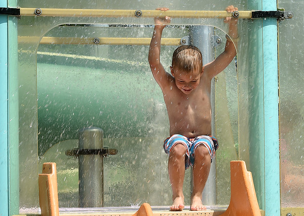 Six-year-old Richard Fraser, of Webb City, cools off with a trip down the kiddie slide on Monday at Schifferdecker Pool. Residents flocked to the pools in large numbers on Memorial Day as temperatures began to heat up.<br /> Globe | Laurie Sisk