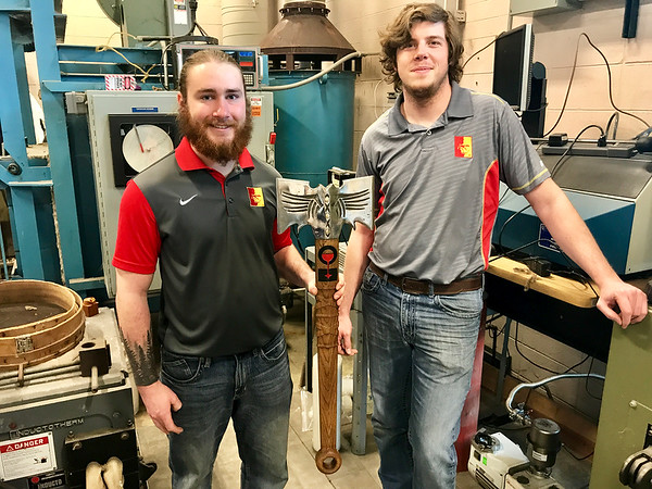 """Logan Roseberry, La Harpe, Kansas, and Michael Paddock, Clinton, Missouri, pose with their nationally award-winning Viking ax in the Department of Engineering Technology at Pittsburg State University. The two won """"Most Captivating Design"""" in the recent national Cast in Steel competition against 15 other universities and 20 Viking axes. That double-headed design included the classic feature design of a Viking ax and included the splitface Gorilla and the event sponsor's logo on the handle. As students of University Professor Russ Rosmait and Professor Jacob Lehman in Manufacturing Engineering Technology, they began their ax complex project in November.<br /> Photo Courtesy PSU"""