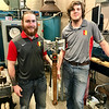 "Logan Roseberry, La Harpe, Kansas, and Michael Paddock, Clinton, Missouri, pose with their nationally award-winning Viking ax in the Department of Engineering Technology at Pittsburg State University. The two won ""Most Captivating Design"" in the recent national Cast in Steel competition against 15 other universities and 20 Viking axes. That double-headed design included the classic feature design of a Viking ax and included the splitface Gorilla and the event sponsor's logo on the handle. As students of University Professor Russ Rosmait and Professor Jacob Lehman in Manufacturing Engineering Technology, they began their ax complex project in November.<br /> Photo Courtesy PSU"