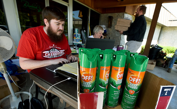 Dwindling supplies of bug spray sit on a table on Thursday at Briarbrook Country Club as volunteer Anthony Ware, left, enters data and Martha Niess, of the Carl Junction Chamber of Commerce coordinates volunteers. An increased number of mosquitoes have challenged volunteers as they clean up from last week's tornado.<br /> Globe | Laurie Sisk