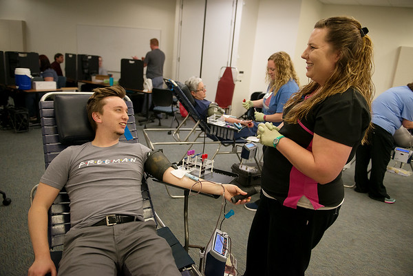 Allison Reynolds, phlebotomist with the Community Center of the Ozarks, talks with Chase Burgess, digital marketing and social media coordinator with Freeman Hospital, during a blood drive at Freeman Hospital on Tuesday.<br /> Globe | Roger Nomer