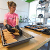 WorkFresh employee Salena Tate assembles a breakfast meal with pancakes at the WorkFresh store on East Seventh Street on Friday. The business offers about 20 meal options using fresh ingredients.<br /> Globe | Laurie Sisk