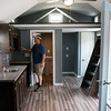 Greg Henry, Rogers, Ark., explores the interior of the modern tiny house up for auction on Tuesday at Crowder Technical Education Center. Henry bought the other rustic tiny house at the auction.<br /> Globe | Roger Nomer