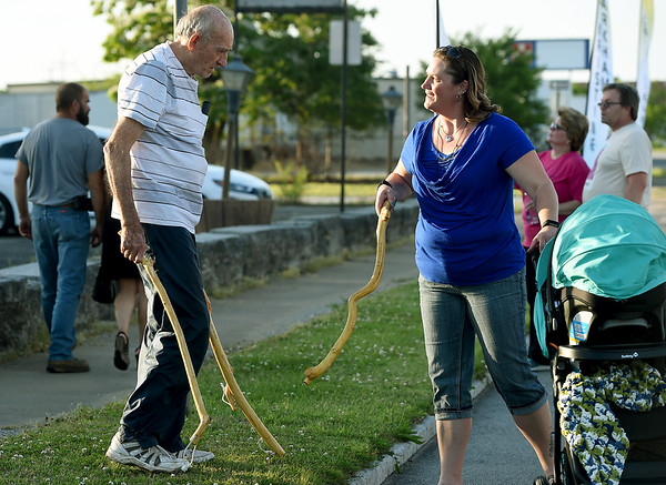 Bob Roberts hands a walking stick to Walk of Silence participant Lisa McCall during the annual walk on Friday night on Joplin Street. Roberts has handcrafted hundreds of the sticks from a corkscrew willow in his backyard and has inscribed the sticks with messages memorializing the May 2011 tornado that took 161 lives.<br /> Globe | Laurie Sisk