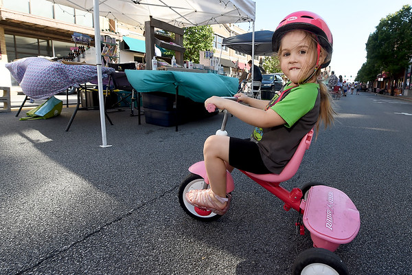 Three-year-old Nora Mudge patrols around her aunt's bath and body booth, Whatever is Lovely, on her tricycle during Third Thursday in downtown Joplin. Mudge was trying to make sure her aunt, Lisa Payne, sold no product because Nora believes they are all belong to her.<br /> Globe | Laurie Sisk