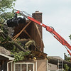 A worker with Disaster Recovery Demolition Services removes a tree from a house in Briarbrook on Friday.<br /> Globe | Roger Nomer