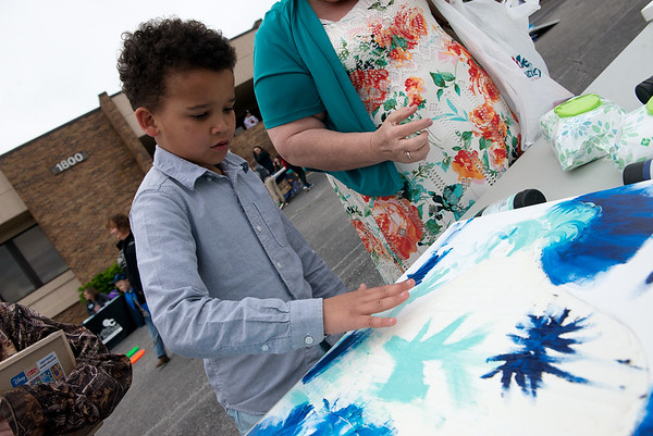 Andres King, 9, contributes to a finger painting on Thursday during the annual Will's Place Block Party. The block party was created as a fun way to discuss the serious topic of mental health, educate the public about children's mental health needs and reduce stigma associated with receiving mental healthcare.<br /> Globe | Roger Nomer