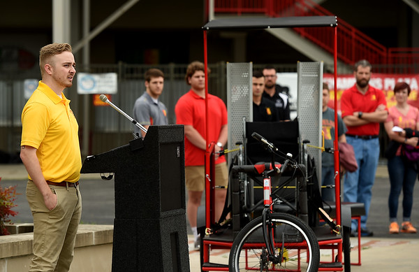 Flanked by other members of the development team, Pittsburg State University senior Mitchell Yeomans, left, talks about the development of the Mechanical and Manufacturing Engineering Technology's new Pedicab on Wednesday at Gorilla Village. The pedicycle allows volunteer pedalers in the Pittsburg community to give rides to wheelcgair bound persons and those with mobility challenges. Yeomans was one of seven PSU students who worked on the project.<br /> Globe | Laurie Sisk