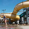 Hailey Myers, pool manager, washes the deck of the Schifferdecker Pool on Friday.<br /> Globe | Roger Nomer