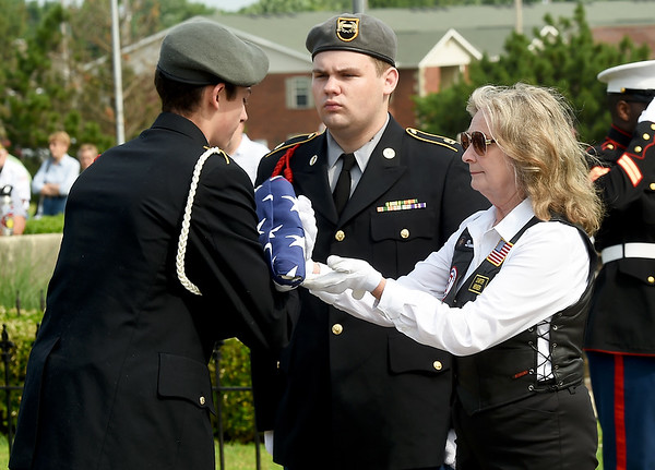 From the left: Joplin High School JROTC cadets Ben Watkins and Jordan Foster accept a flag from American Legion Freedom Rider Danette Bray honoring one of three veterans during a special Memorial Day service at Mount Hope Cemetery. Veterans Morris M. Boyd, Ralph P. Lane and Glenn R. Lake received full military rites on Monday.<br /> Globe | Laurie Sisk