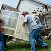 Keith James, center, hurrys to move a cabinet out of his house before the roof collapses further in the Briarbrook neighborhood of Carl Junction on Thursday.<br /> Globe | Roger Nomer