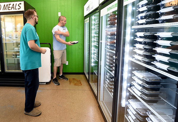 WorkFresh employee Adam Marold, right,  assists customer Stephen Rose as he looks through the variety of freshly prepared meals at the WorkFresh store on East Seventh Street on Friday. The business offers about 20 meal options using fresh ingredients.<br /> Globe | Laurie Sisk