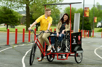 Pittsburg State University senior Mitchell Yeomans takes PSU graduate Jordyn Bollinger on a ceremonial first ride in the Mechanical and Manufacturing Engineering Technology's new Pedicab on Wednesday at Gorilla Village. The pedicycle allows volunteer pedalers in the Pittsburg community to give rides to wheelcgair bound persons and those with mobility challenges. Globe | Laurie Sisk
