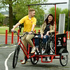 Pittsburg State University senior Mitchell Yeomans takes PSU graduate Jordyn Bollinger on a ceremonial first ride in the Mechanical and Manufacturing Engineering Technology's new Pedicab on Wednesday at Gorilla Village. The pedicycle allows volunteer pedalers in the Pittsburg community to give rides to wheelcgair bound persons and those with mobility challenges.<br /> Globe | Laurie Sisk