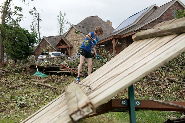 Janell Franks clears debris from her yard in Briarbrook on Tuesday.<br /> Globe | Roger Nomer