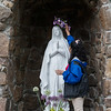 Indira Madrigal, McAuley High School senior, places a flower crown on the statue of Mary at the McAuley grotto on Thursday.<br /> Globe | Roger Nomer