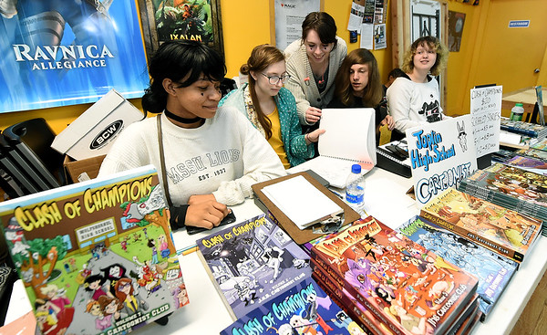From the left: Joplin High School Cartoonist Club's Antwanice Perry, Jeana Barham, Zoe Angelopoulos, Jesse Hodge and Emily Koehler sell copies of their comic books during Free Comic Book Day on Saturday at Hurley's Heroes. Proceeds from the sale will allow production of more comic books by the group. Globe | Laurie Sisk