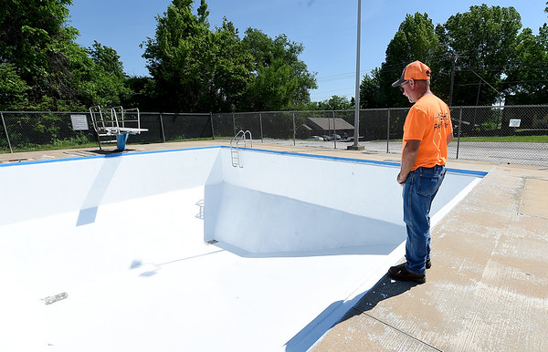 Neosho Parks and Recreation Supervisor Kenny Balls inspects the freshly painted Neosho City Pool as workers ready the pool for the public.<br /> Globe | Laurie SIsk