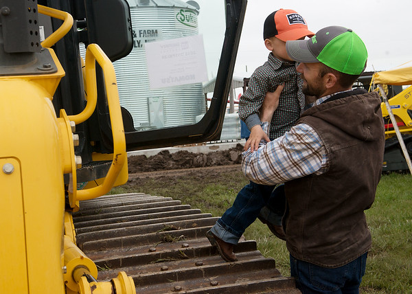 Daniel Webb, Decatur, Ark., lifts his son Graham, 3, from a tractor at the Four State Farm Show on Friday near Pittsburg.<br /> Globe   Roger Nomer