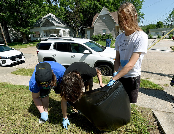 From the left: John Olds, devan Laughlin and Austin Stoffel clean up trash around the Neosho High Schoool Jefferson Street Campus on Thursday as members of the Clean Community Project.<br /> Globe | Laurie Sisk