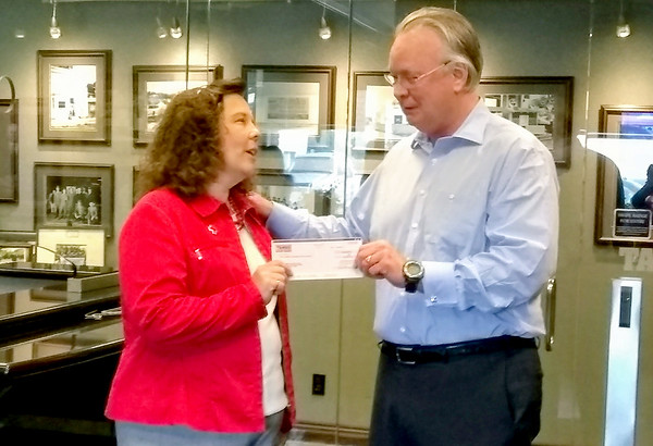 David Humphreys, president and CEO of TAMKO Building Products, hands a $100,000 check to Stacy Burks, executive director for the American Red Cross of Southern Missouri, on Friday. The donation will be used for disaster relief operations in Jasper, Newton and Barton Counties. Kimberly Barker/JoplinGlobe