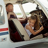 "Sophie Tyson, 7, Monett, checks out how different parts of an airplane move during a tour with Ernie Trumbly, aerospace education officer with the Civil Air Patrol, on Saturday at the Alpha Air Center. Girl Scouts of the Missouri Heartland toured the airport and received an education in flight during the ""Who Wants to be a Pilot"" event."