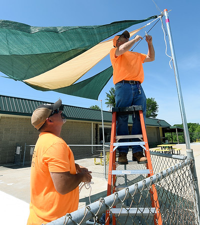 Neosho Parks and Recreation Supervisor Kenny Balls, right, installs a sun shield over the kiddie pool at the  Neosho City Pool as workers ready the pool for the public.<br /> Globe | Laurie SIsk