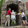 Madison Childs, left, and Medland Wallace, McAuley High School seniors, help place flowers at the McAuley grotto on Thursday.<br /> Globe | Roger Nomer